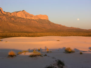The western escarpment, once a reef in a shallow sea and now among the highest points in Texas, and a nearly full moon still. (NPS photo)