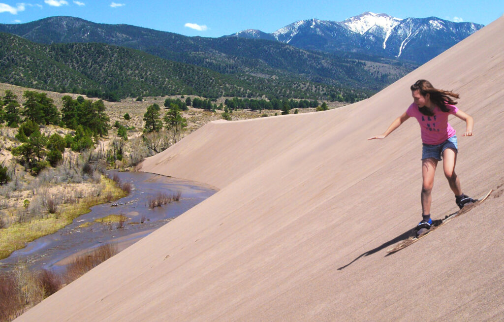 A teenaged girl sandboards down a dune overlooking a blue creek lined by cottonwoods, with snowcapped mountains in the distance.