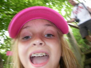A pre-teen girl in a pink hat taking a selfie in the woods