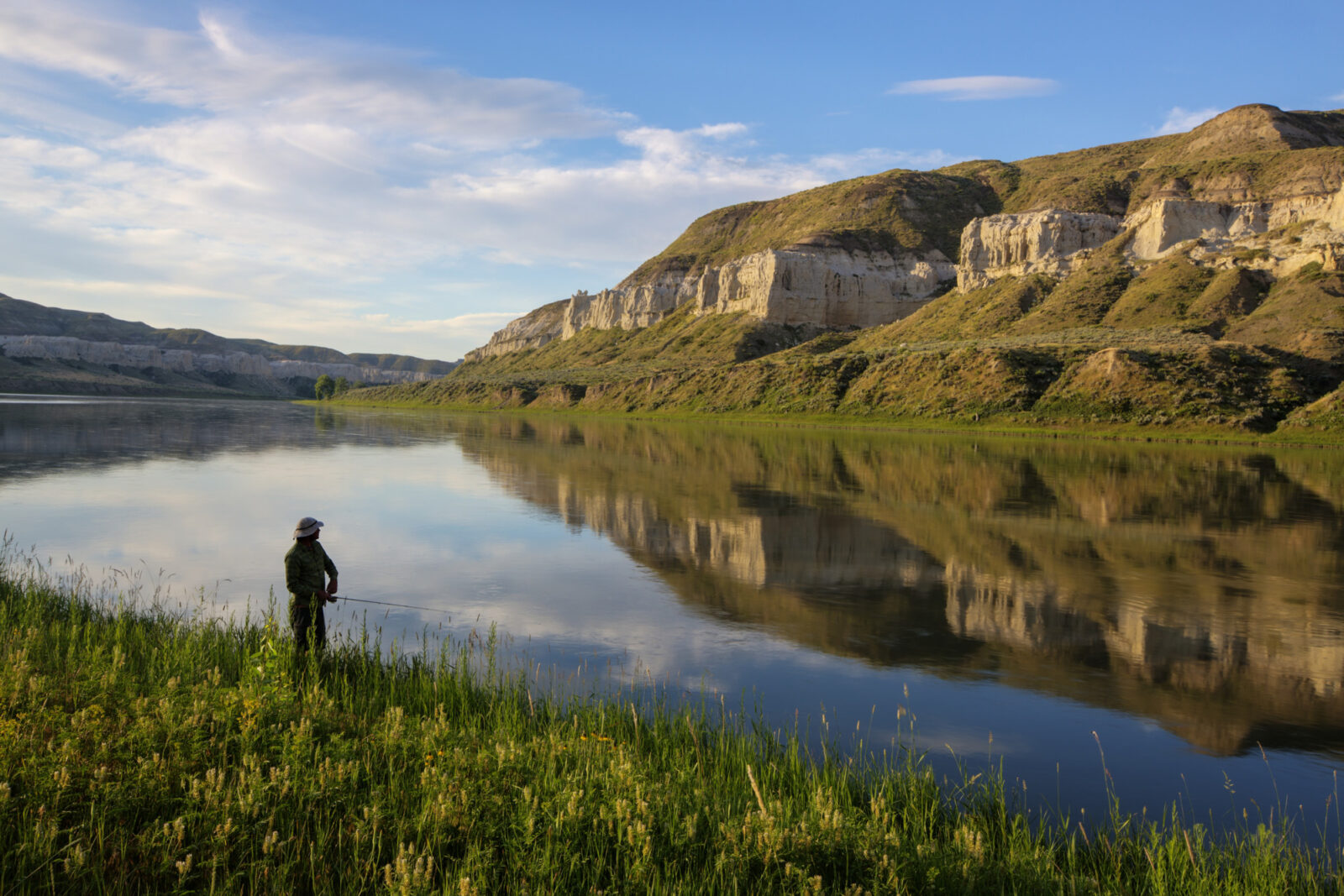 A photo of a fisherman along the river, with towering bluffs across the stream